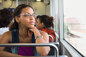 A female domestic violence victim is on the bus staring blankly into the distance.