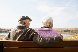 An elderly couple sitting close together looking out into the distance.